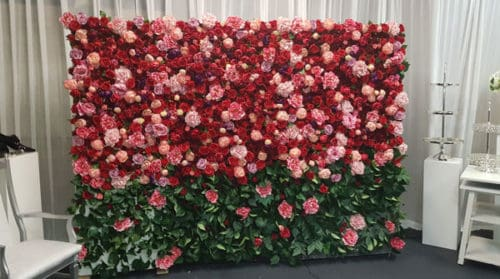 red and pink flowers with green foliage flower wall