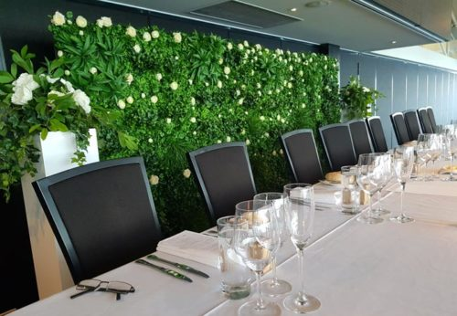 lush green flower wall with white roses behind reception table