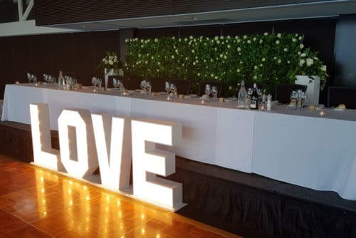 green flower wall with love sign