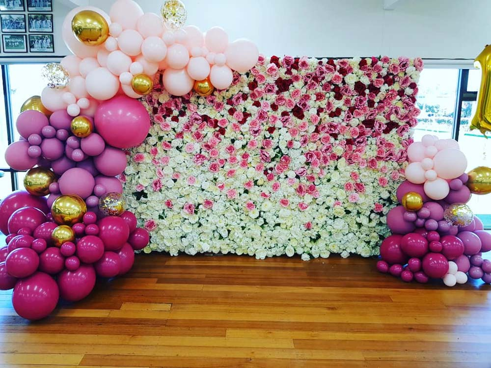 balloons styling around white and pink flower wall